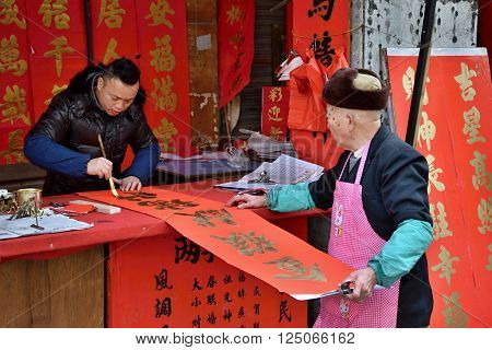 "FOSHAN, CHINA - CIRCA JANUARY 2016: calligraphers are writing spring couplets (""chunlian"
