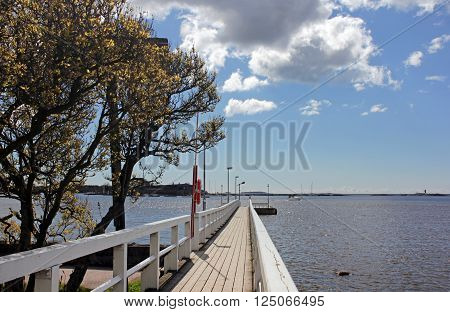 Wooden footbridge to pier at Baltic sea in spring sunny day Helsinki Finland.