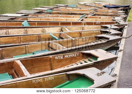CAMBRIDGE ENGLAND - MAY 9 2015: Flat bottom boats or punts with colorful names are commonly used to transport tourists along the River Cam in Cambridge England.