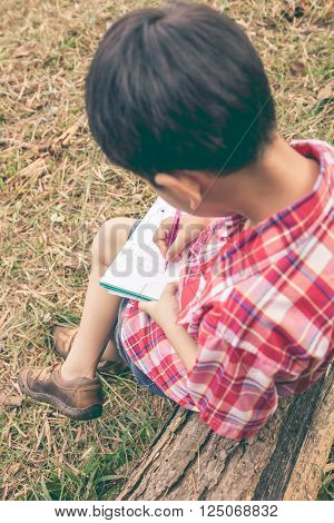Back view. Child use pen to drawing on notebook on wooden log in park at the day time with bright sunlight. Use it for outdoors learning or education concept. Vintage style.