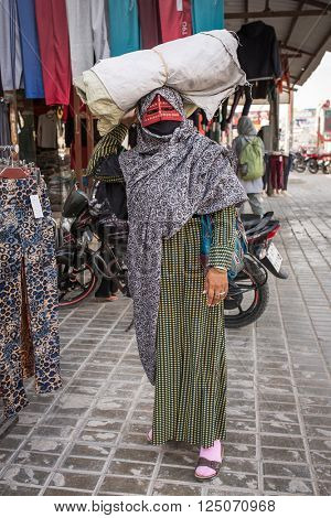 Qeshm, Iran - December 21, 2015: Bandari woman wearing a traditional mask called the burqa, Qeshm Island, Salakh, Iran
