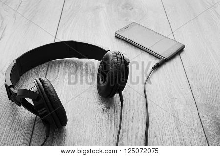 Black smartphone and black headphones on wood background. Selective focus on right earpiece of headphones. Black and white.