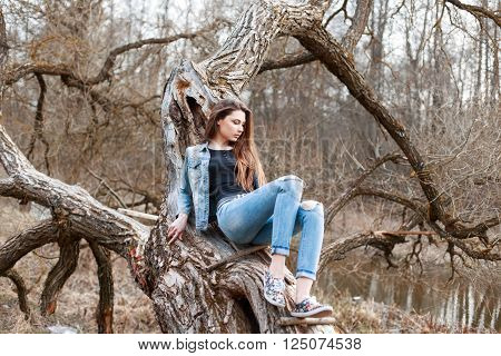 Beautiful Girl In Jeans Jacket And Denim Shorts Sitting On A Tree. Relax In Nature.