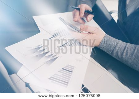 Photo account manager working at the table with new startup project.Holding modern smartphone hand, touching screen. Signs document and analyze plans