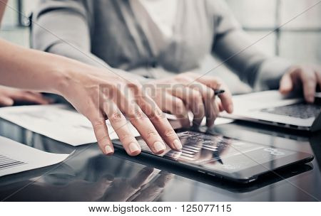 Analytical department working process.Closeup photo woman showing business reports modern tablet screen.Statistics graphics screen.Banker holding pen signs documents, discussion startup. Horizontal