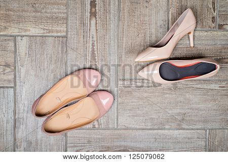 Overhead view of girl's shoes on wooden background