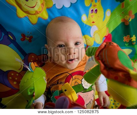 Excited happy smiling small three months old baby boy playing in colorful playpen. Selective focus on the baby. Heavy vignette.