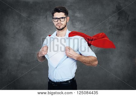 Like a superhero. Confident young man with superhero cape taking of his shirt and looking at camera while stabnding against concrete wall