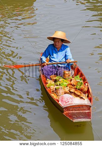 RATCHABURI, THAILAND - FEB 20: A woman serves Thai food at Damnoen Saduak floating market on February 20, 2011 in Ratchaburi, Thailand. The local market is popular for traditional food and souveniers.