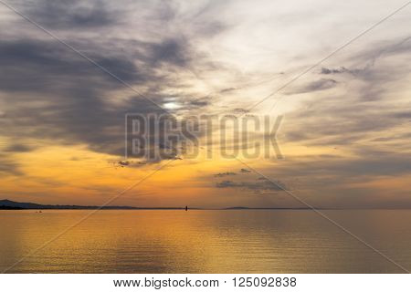 A cloudy sunset over a lake with a sail in the distance