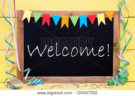 Chalkboard With English Text Welcome. Party Decoration Like Streamer, Confetti And Bunting Flags. Yellow Wooden Background With Vintage, Retro Or Rustic Syle