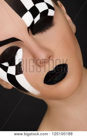 face of young woman with black and white pattern on black background