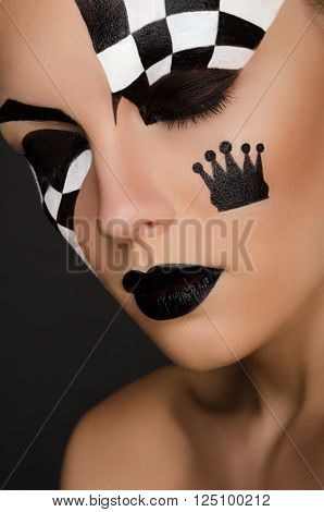 portrait of beautiful woman with black and white face art on black background