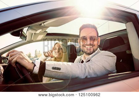A young woman and a young man are laughing in the car enjoying in the road trip. The man is driving.