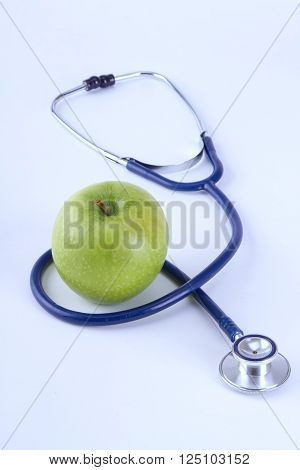 Medical stethoscope and apple isolated on white background.