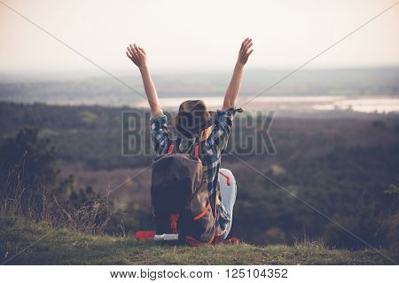 Young woman watching landscape, posing outdoor. Active lifestyle concept.  Arms up.