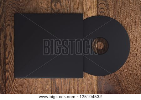 Topview of blank black compact disk with cover on wooden table. Mock up 3D Rendering