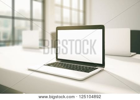 Sideview of white office desktop with blank laptop screen. Mock up 3D Rendering