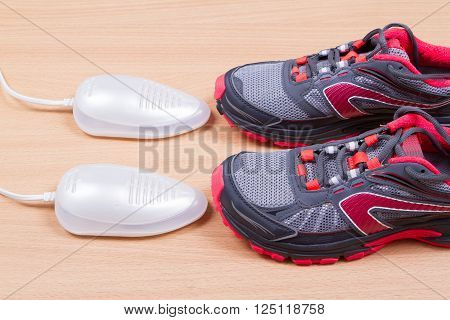 Electric ultraviolet shoe dryer and Sneakers. isolated on wooden background.