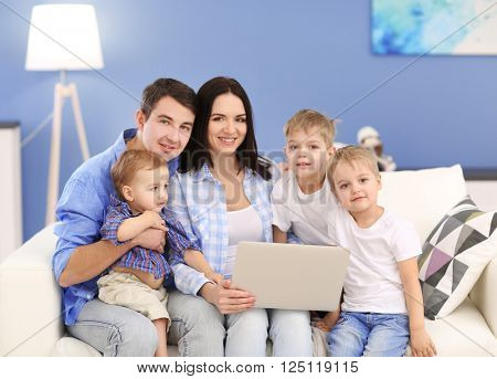 Family concept. Happy family with laptop on sofa in the room