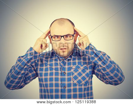 Man with glasses holding his head with his hands. Stress, neurosis, disorder .Isolated on a gray background.