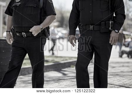 officers law enforcement police in uniform with weapons guns walking on patrol