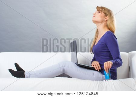 Angry woman using laptop sitting on sofa and throwing credit card, paying over internet for online shopping, computer or payment problem, surfing internet, modern technology
