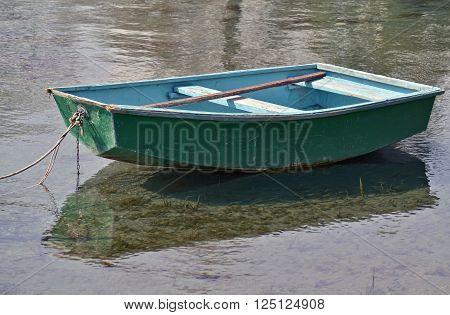 Small green rowboat moored at the shore of the lake