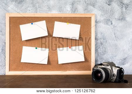 Blank papers pin up on cork board and a camra over a wooden table with a textured background.