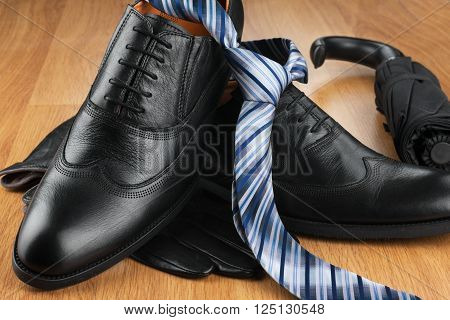 Classic men shoes tie gloves umbrella on wood can be used as background