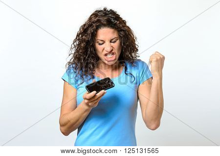 Emotional woman holding a broken mobile phone reacting in anguish or frustration with closed eyes and open mouth