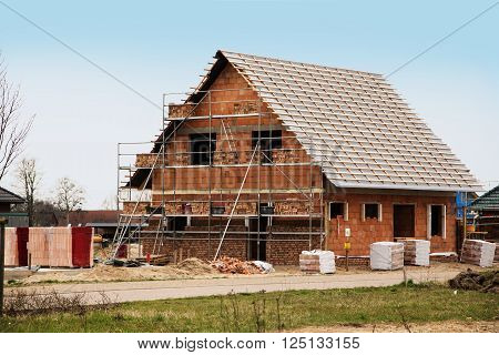 new home under construction building a European style house stone on stone