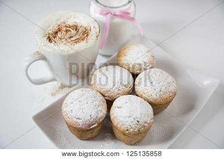 Freshly baked homemade muffins with powdered sugar and coffee