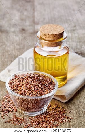 Bottle of linseed oil and bowl of linseeds on wooden background