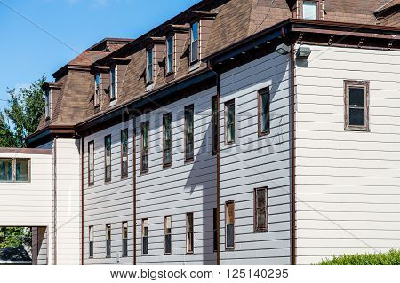 Old White Siding Apartment with Mansard Roof in Canada