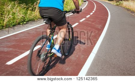 a cyclist in motion on a rode at summer