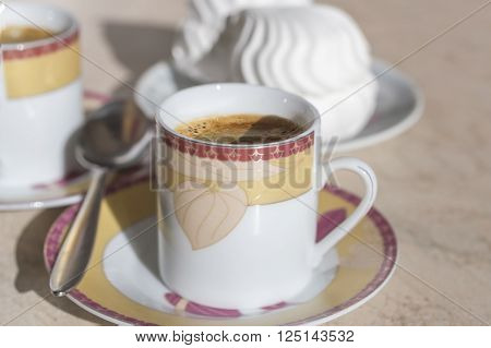 A cup of coffee with crema, spoon and cake.