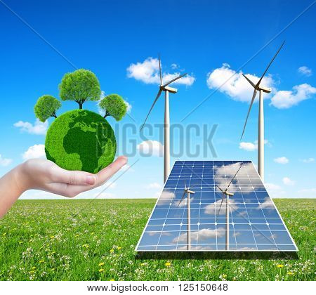 Solar energy panels with wind turbines and green planet in hand. Concept of environmental protection.