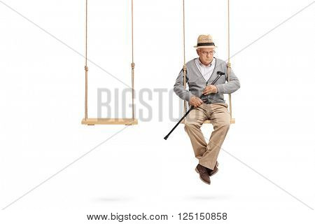 Lonely senior sitting on a wooden swing with an empty swing next to him isolated on white background