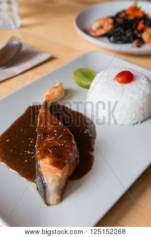 Salmon teriyaki sauce served with white rice and lime