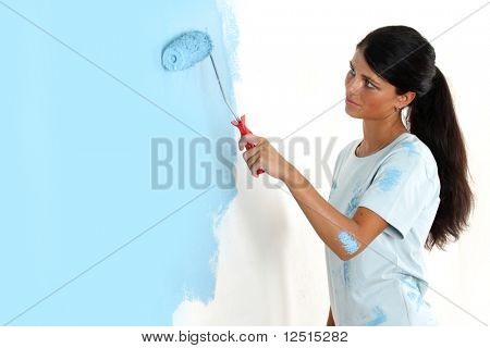 roller in woman hand paint on the wall