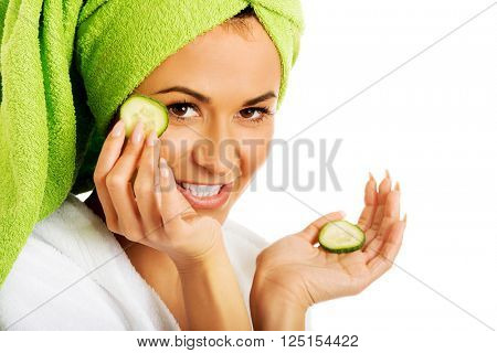 Woman in bathrobe applying cucumber on eyes