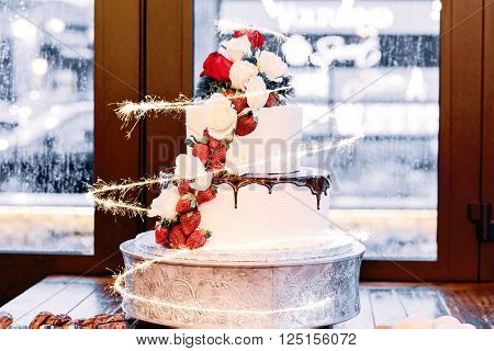 A 3 tiered cake with strawberries and a sparkler around it. Rainy background