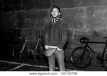 Modern young man posing on a background of city bikes at night. Black and white portrait of a modern urban dweller