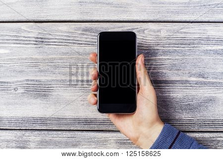 Blank black smartphone held by male hand on wooden background. Mock up