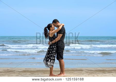 Romantic couple on beach.Young happy interracial couple standing and embracing each other on beach. Asian womanCaucasian man