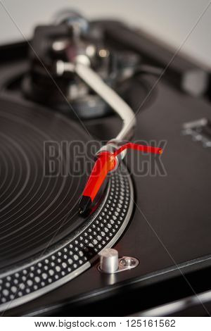 Turntable playing analog audio vinyl disc with music. Close up on record tonearm and needle macro photo. Professional audio equipment for DJ nightclub or audio enthusiast.