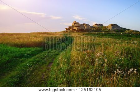 The stone remnants of old sanctuary enclosed by wooden fence near the Big Allaki lake in Southern Urals Russia. Selective focus at the stone remnants. Summer landscape in soft sunset light. Soft filter applied