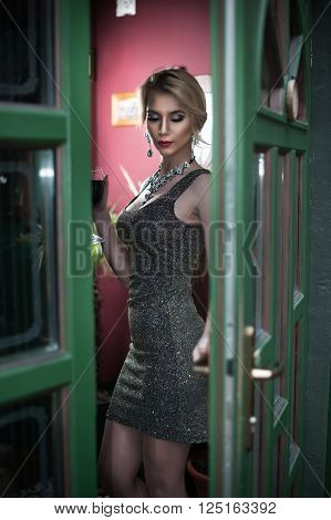 Charming young blonde with silver short tight fit dress posing in a green painted door frame. Sensual gorgeous young woman in gray outfit with accessories, opening the door for somebody with sad look