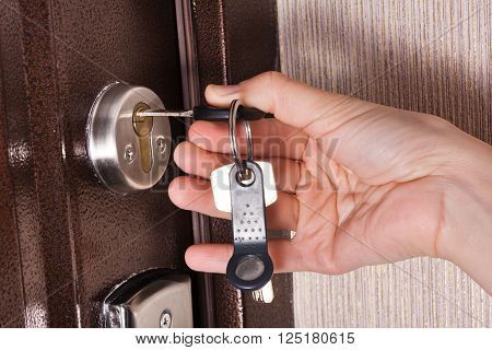 hand unlocking front door lock of house clouseup